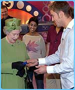 Presenter Simon Thomas gives the Queen a gold Blue Peter badge