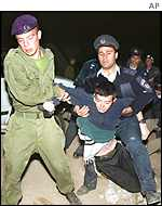 Israeli military police forcibly remove a Jewish settler