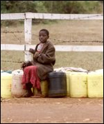 Boy guarding water tubs in Nairobi suburb