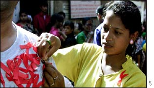 A sex worker in India pinning an Aids ribbon
