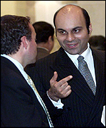 Mostafa Zahir of the Rome faction (right) chats with an unidentified delegation member at the talks