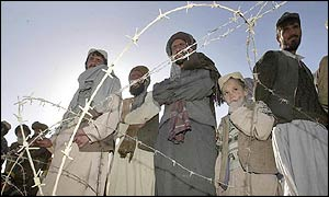 Men next to barbed wire fence