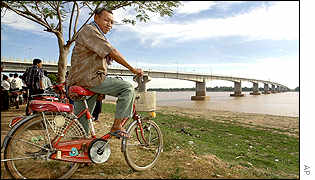 Cambodian man on his bike looks at the newly built bridge on the Mekong River