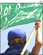 A hooded Palestinian boy holds a Hamas flag