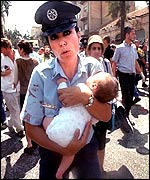An Israeli policewoman carries a baby to safety at the scene of the blast