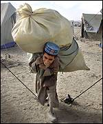 A boy carries aid provisions in the UNHCR camp near Chaman border crossing