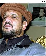 Mohammad Fahim with portrait of Masood in background