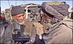 Two Afghan men in Kabul listen to a radio