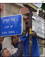 Workmen put placard on Jerusalem Street renaming it New York Street