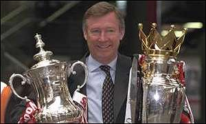 Alex Ferguson poses with the FA Cup and Premiership trophy in 1996