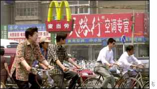 Chinese cyclists pass McDonalds sign