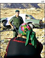 An Israeli soldier prevents a Palestinian woman from approaching a car that was attacked