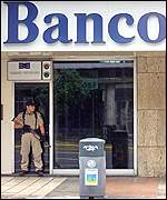 A policeman guards the entrance to a bank