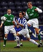 Hibs skipper Franck Sauzee challenges for the ball