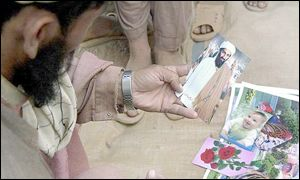 Afghan refugee holding postcard of Bin Laden