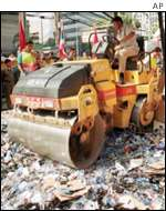 Thai police use a steamroller to destroy counterfeit CDs