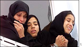 Women in Khan Yunis watch the funeral procession for four men killed in Israeli helicopter attack