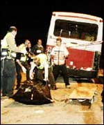Emergency workers remove the body of one of the Israelis killed in the attack