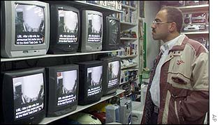Palestinian man watches Osama Bin Laden video tape in a shop in Gaza City