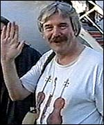 Mike Bussell waves to cameras at Luton airport