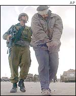 An Israeli soldier leads a blindfolded Palestinian man