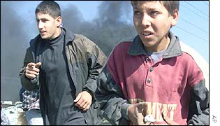 Boys carrying stones escape Israeli army fire