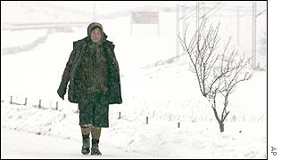A woman walks on a snow-covered road near the capital of Macedonia - Skopje
