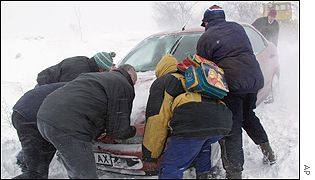 Passengers trying to pull their car from snow on the road from the Black Sea port of Varna