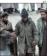 A captured foreign member of al-Qaeda is led by two Afghan anti-Taleban fighters