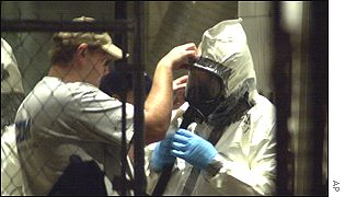 Anthrax worker has his suit sealed with tape by another co-worker in Hart building