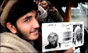 Afghan fighters display reward leaflet dropped by the Americans