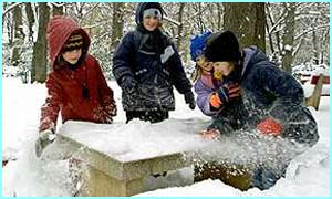Children free an outdoor chess board from snow in Budapest, Hungary