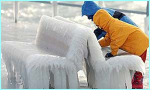 Children touching a bench covered by ice at the walkway bordering the lake of Geneva in Nyon
