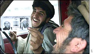 Afghan anti-Taleban fighters returning from Tora Bora share a laugh as they hold up a leaflet they found