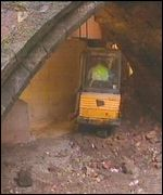 A digger works under a bridge arch