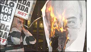 A striking worker watches a poster of Economy Minister Domingo Cavallo burn