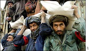 Afghan men carry sacks of wheat
