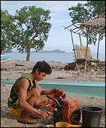 Subsistence fisherman in Mabini repairs his boat engine