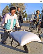 An Afghan youth wheels food aid on a cart