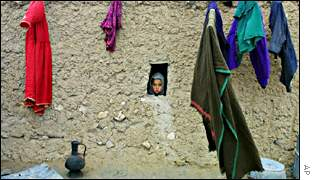 A girl looks out the window of her house in Mazar-e-Sharif
