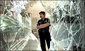 Policeman stands by a smashed window