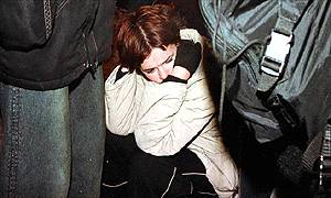 Grieving teenager flanked by police outside the nightclub in Sofia, Bulgaria