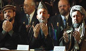 Afghan leader Hamid Karzai (centre) prays with General Muhammad Fahim (left), defence minister of Afghanistan