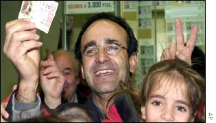 A man holds his winning ticket in Spain