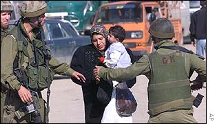 Israeli troops stop a Palestinian at the Kalandia checkpoint, south of Ramallah.