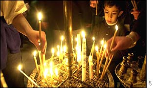 Child lighting a candle in Bethlehem