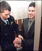 A bailiff puts handcuffs on Mr Pasko after sentencing