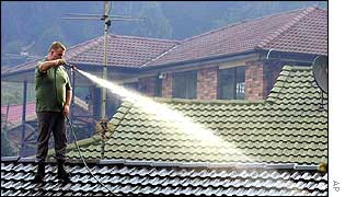 Man uses hose to water roof