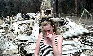 Resident cries in the ruins of her home on the outskirts of Sydney