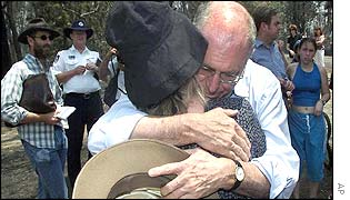 Prime Minister John Howard consoles woman who lost her home